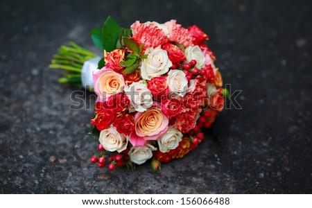 Bouquet of various flowers on asphalt
