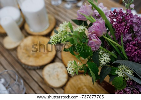 Bouquet of violet lilac and tulips stands on the wooden decor on the table #737677705