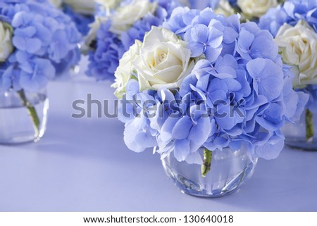 Bouquet of white and blue flower in vase of glass. Decoration of dining table.