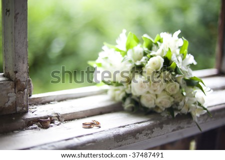 stock photo bouquet of white flowers and 2 wedding rings lying on an old
