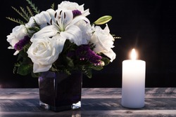 Bouquet of white flowers in a purple vase, white candle on a wooden boards. Vintage home decor dark tones. Condolence card.