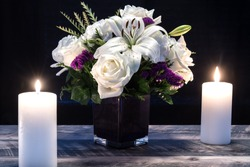 Bouquet of white flowers in a purple vase, white candle on a wooden boards. Vintage home decor dark tones. Condolence card or Valentines Card.