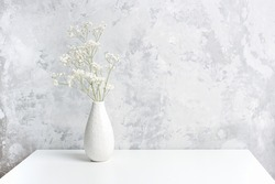 Bouquet of white small delicate flowers gypsophila in vase on table agains gray stone wall. Copy space Minimal style. Template for postcard, text, design Concept Women's day, Mothers Day.