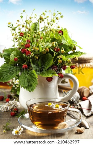 bouquet of wild strawberry with herbal tea and honey - bio food or health concept