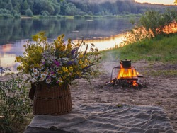 Bouquet of wildflowers and campfire on a background of river