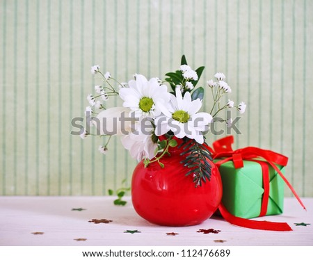 Bouquet of winter flowers with present decorated with ribbon