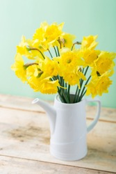 Bouquet of yellow daffodils in white ceramic jar, spring symbol, Easter pastel colors, bunch of flowers on wooden table, light green background, table decoration copy space
