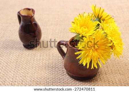 Bouquet of yellow fresh flowers of dandelion in brown vase and empty vase in background lying on jute canvas