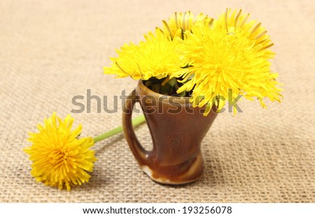 Bouquet of yellow fresh flowers of dandelion in brown vase standing on jute canvas