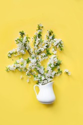 Bouquet white flowers blooming cherry fruit tree in vase on yellow. View from above. Flat lay.