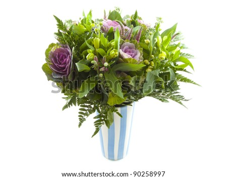 Bouquet with different kind of flowers in blue white vase over white