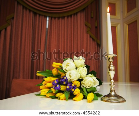 Bouquet with roses near a candle