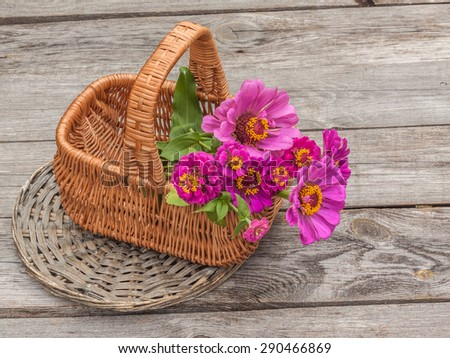 Bouquet with zinnia in a basket on an old wooden table