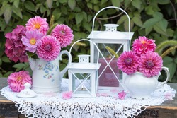 bouquets of pink dahlias and white lantern as garden decoration