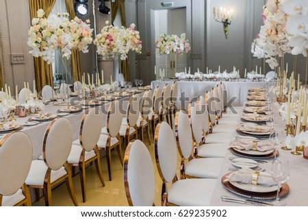 Bouquets of white orchids and pink roses put in vases stand on long dinner tables Сток-фото ©
