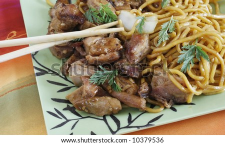 bourbon beef and chinese noodles on decorative plate with chopsticks