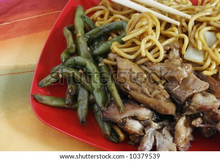 bourbon beef, string beans and chinese noodles on red plate with chopsticks