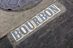 Bourbon Street tile signage on street next to manhole in New Orleans, Louisiana French Quarter