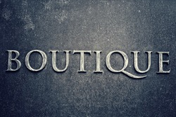 Boutiques sign on a metal plate. Business concept