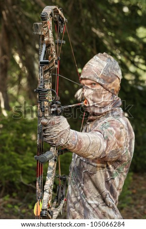 bow hunter in camouflage pulling bow back closeup