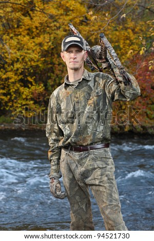 bow hunter standing by river in fall