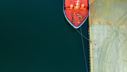 Bow of a cargo ship at port with mooring lines securing the vessel to the bollards on the dock. Aerial view.