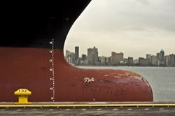 bow of large ship with draft scale numbering , large african city in the background (durban, south africa)