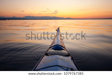 Bow of sea kayak at sunset pointed at Bainbridge Island and the Olympic Mountains, Puget Sound, Seattle, WA USA