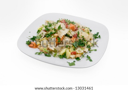 Bow tie pasta salad on plate isolated on white with clipping path. Salad has chick peas, carrots, summer squash, red pepper and parsley.