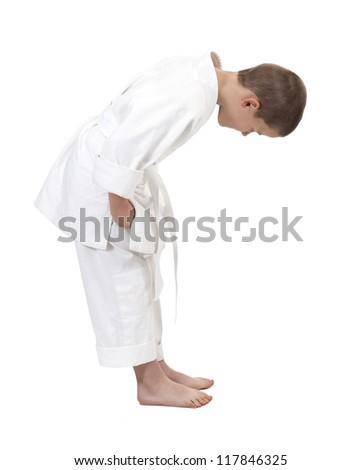 bowing boy in judo kimono, isolated on white