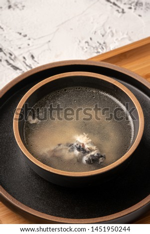 Bowl and bowl of chicken soup in a plate on a marble tabletop