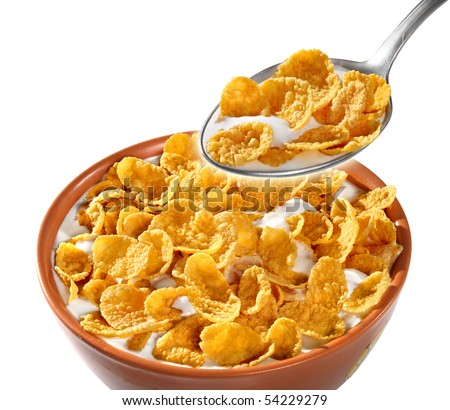 Bowl and spoon with corn flakes on the white background - stock photo