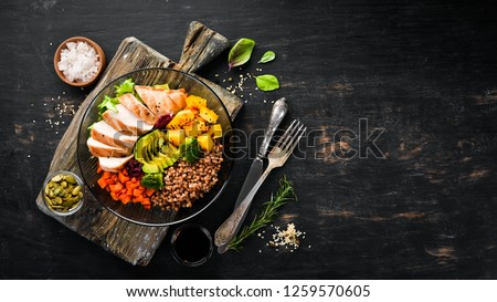 Bowl Buddha. Buckwheat, pumpkin, chicken fillet, avocado, carrots. On a black background. Top view. Free space for your text.