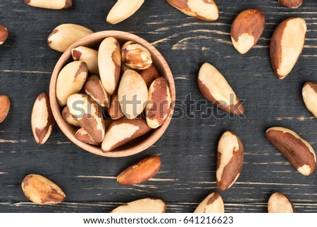 Bowl filled with Brazilian nuts on a wooden background, top view