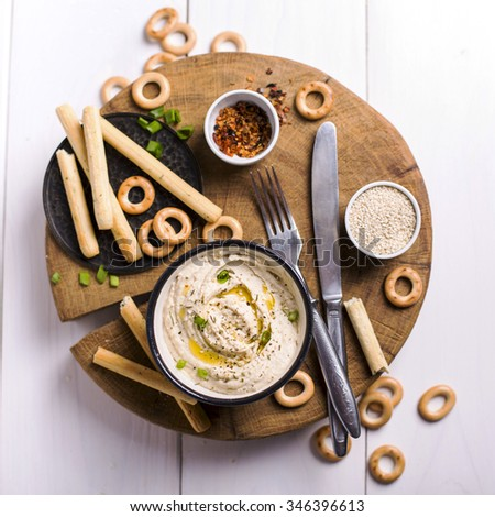Bowl full of classic hummus with crispy bread sticks shot from above ストックフォト ©