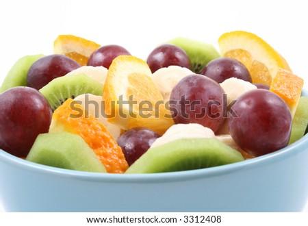 bowl full of delicious fruit salad - kiwi banana orange and grapes - isolated on white