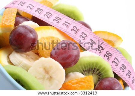 bowl full of delicious fruit salad - kiwi banana orange and grapes - isolated on white