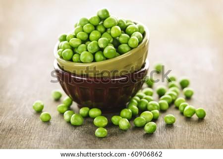 Bowl full of fresh green organic green peas - stock photo