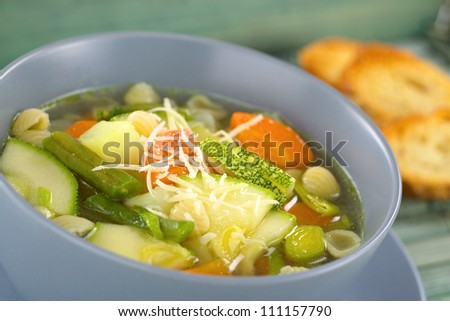Bowl full of fresh vegetarian Italian minestrone soup made of green beans, zucchini, carrots, potatoes, leek and shell pasta with grated cheese on top (Selective Focus, Focus one third into the soup)