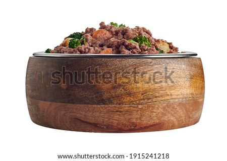 Bowl full of healthy premium homemade pet food for dogs and cats with ground meat or barf mixed with assorted fresh vegetables in a low angle side view isolated on white Foto d'archivio ©