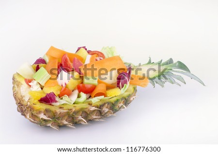 bowl made from the peel of pineapple with fruit salad and vegetables Salad,