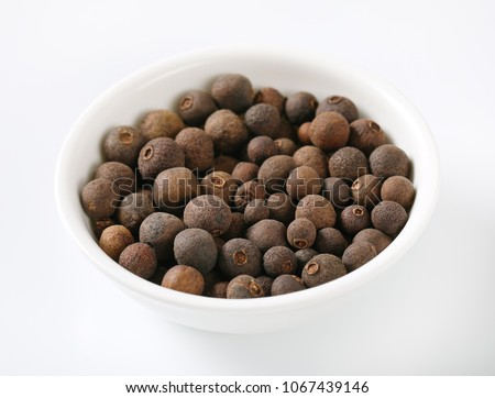 bowl of allspice berries on white background #1067439146