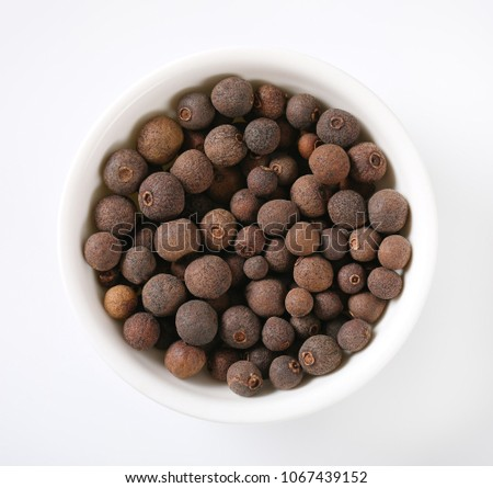 bowl of allspice berries on white background #1067439152