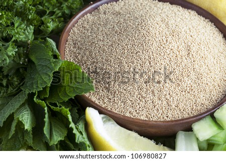 Bowl of amaranth seeds surrounded by mint, parsley and a lemon wedge. - stock photo