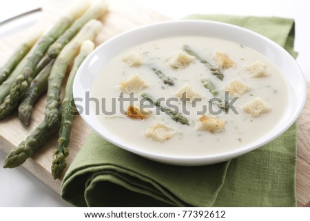 Bowl of asparagus soup with croutons on white background