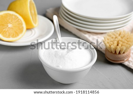 Bowl of baking soda, brush and lemon on light grey table Photo stock ©