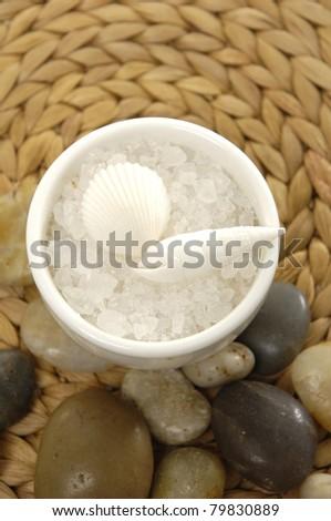 Bowl of bath salt with seashell and pebbles on woven mat