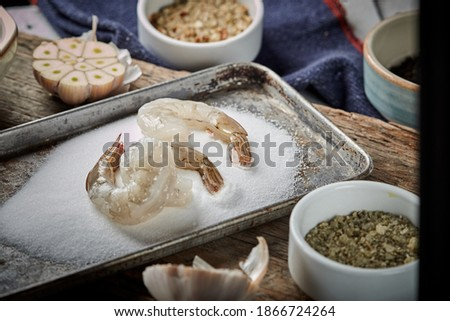 bowl of boiled raw gambas isolated in salt on wood background Foto d'archivio ©