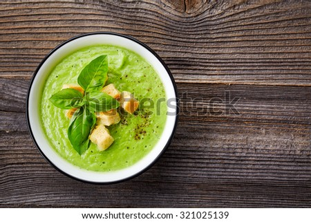 bowl of broccoli and green peas cream soup on wooden table, top view