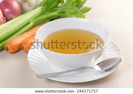 bowl of broth and fresh vegetables on wooden table #246171757
